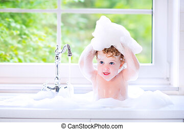 Funny baby girl playing with water and foam in a big kitchen...