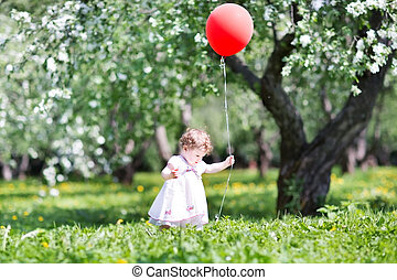 Funny baby girl walking in an apple tree garden with a red ballo