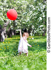 Funny baby girl with a big balloon