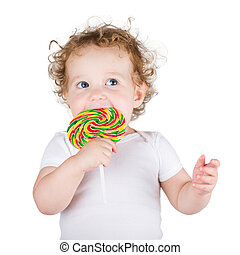 Funny baby girl with a big colorful candy