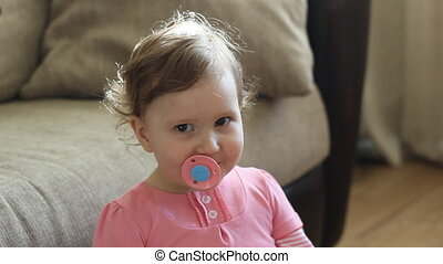 Funny baby girl with a pacifier