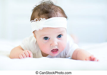 Funny baby girl with a white bow