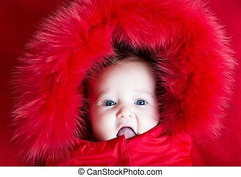 Funny baby girl with beautiful blue eyes in a warm winter jacket