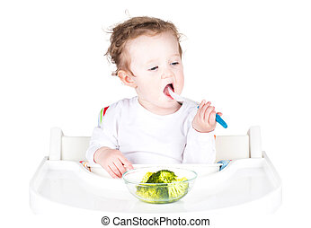 Funny baby having lunch in a white chair