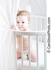 Funny baby in a diaper playing in its crib