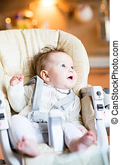 Funny baby in a high chair