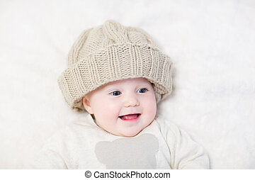 Funny baby in a huge knitted hat