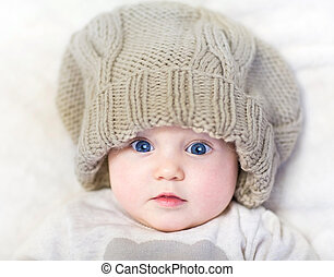 Funny baby in a huge knitted hat wearing a warm sweater