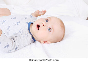 Funny baby infant child with blue eyes lying on the bed