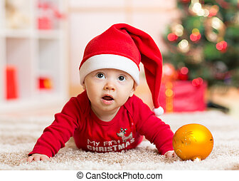 Funny baby lying on tummy wearing Santa hat and suit in...