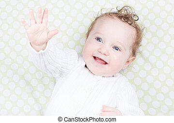 Funny baby playing on a green blanket