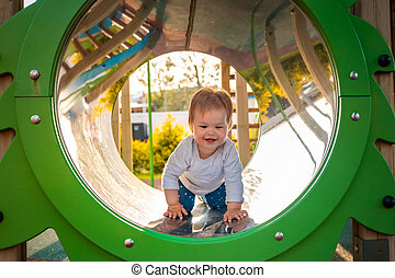 Funny baby playing on the playground, crawls in a tube. Outdoors. Concept of autism