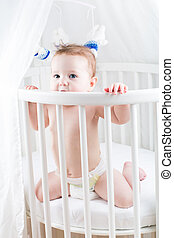 Funny baby sitting in a round white crib