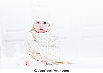Funny baby sitting in a white bedroom wearing a warm knitted scarf and hat