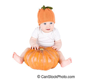 Funny baby sitting next to a pumpkin wearing a knitted pumpkin hat, isolated on white
