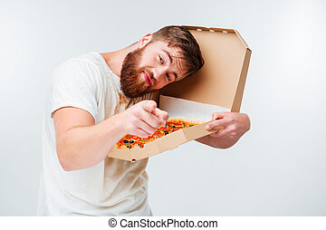 Funny bearded man holding pizza box and pointing at camera