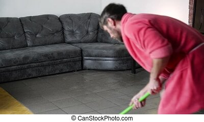 funny bearded man in a pink bathrobe washes tiled floor