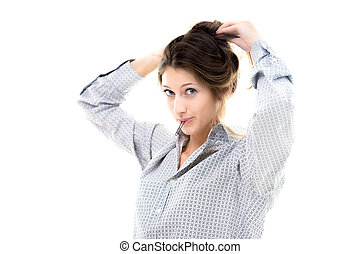 Beautiful young girl holding hairpin in her lips tying hair back, making hairdo with playful expression, copy space