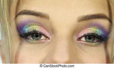 funny beautiful woman with colorful makeup moves her...