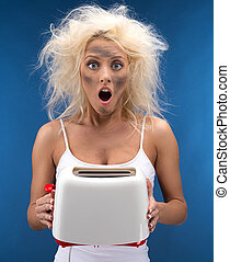 Funny blond girl having trouble with toaster. Isolated on blue