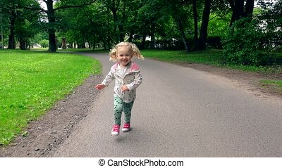 Funny blond girl with pigtails running through park road in...