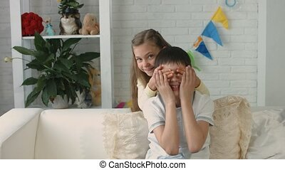 Funny boy and girl of school age spending time at home