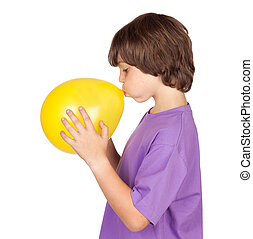 Funny boy blowing up a yellow balloon isolated on white...