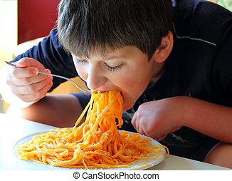Funny boy eating spaghetti.