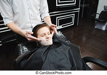Funny boy in a black salon cape in the barbershop.