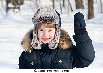 Funny boy in a fur hat on a cold sunny winter day