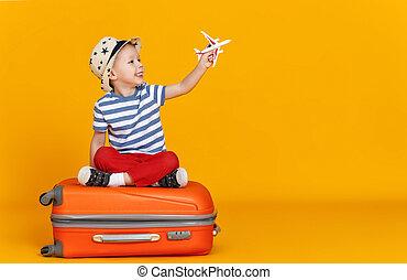 Funny boy sitting on suitcase