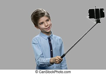 Funny boy using monopod on gray background.