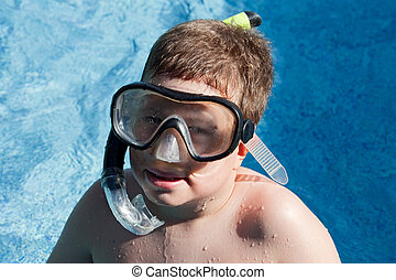 Funny boy with diving goggles and snorkel swimming in the water