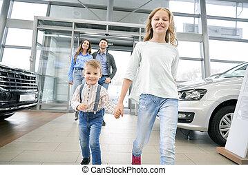 Funny boy with elder sister entering in big auto showroom
