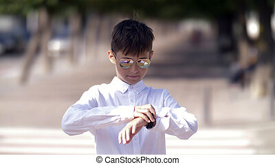 Funny boy with glasses looks at watch in the street