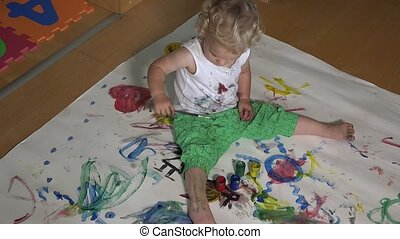Funny boy with paintbrush painting on paper and clothes.