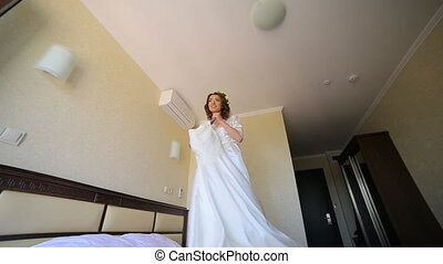 Funny bride is dancing with wedding dress in the dark room
