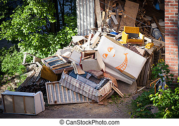 Funny broken furnitures trash pile at yard
