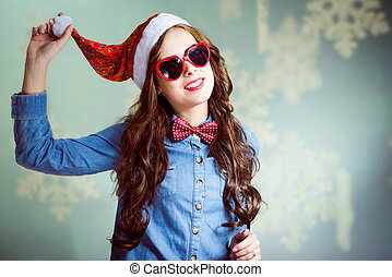Funny brunette girl in Christmas hat and heart-shaped glasses