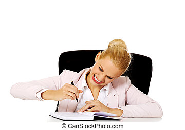 Funny business woman taking notes behind the desk