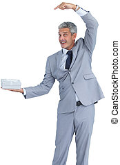 Funny businessman holding gift in right hand