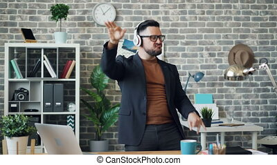 Funny businessman relaxing at work listening to music in headphones dancing