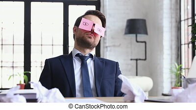 Funny businessman sleeping at workplace with sticky notes on...