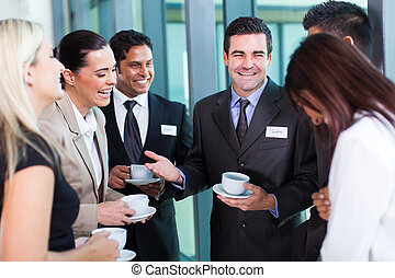 funny businessman telling a joke during conference coffee...