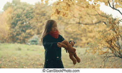 funny, cheerful cute little girl spinning with her toy, teddy bear yellow in the amazing autumn park slow motion