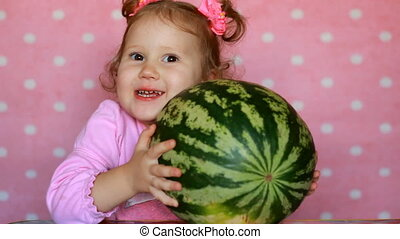 Funny cheerful happy little girl holding a big watermelon....
