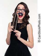 Funny cheerful woman having fun using glasses and moustache ...