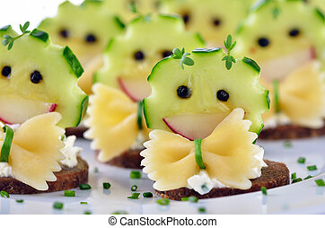 Funny morsels with spicy cream cheese, decorated with cucumber, radishes, pasta and pepper
