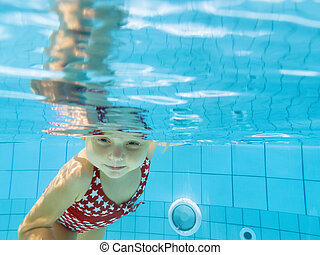 Funny child dive underwater in swimming pool
