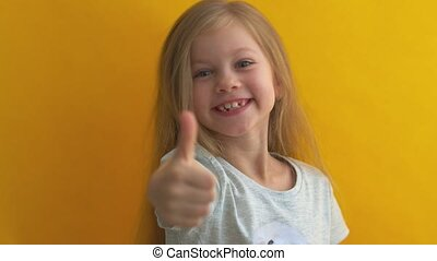 Funny child girl against an yellow background showing number two, symbol of counting, concept of mathematics, confident and cheerful